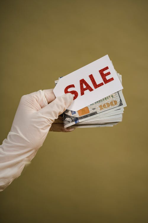 Person Holding Cash Money And Sale Tag