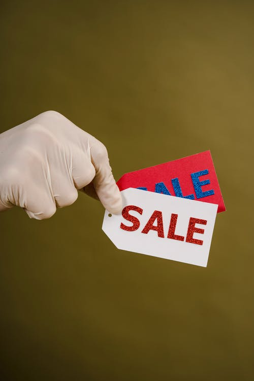 Person Holding Red And White Sale Tags