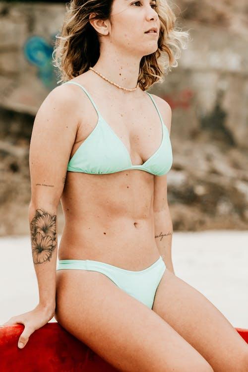 Woman in Teal Bikini Standing on Sand
