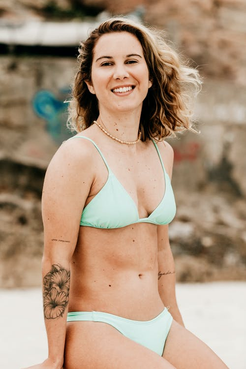 Cheerful traveler in swimwear on coast in summer