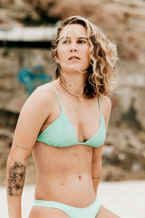 Woman in Teal Bikini Top Standing on Brown Soil
