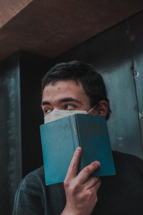 Man in Black Shirt Holding Green Hardbound Book