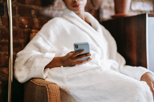 Crop anonymous ethnic female in bathrobe text messaging on cellphone while resting in armchair in beauty salon