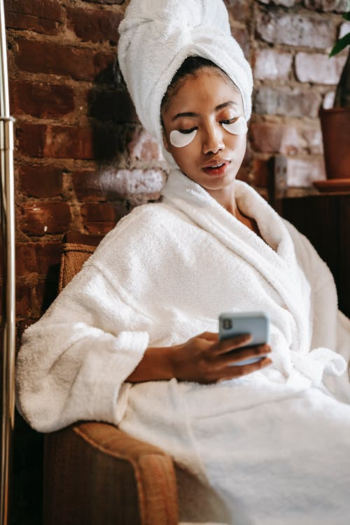 Ethnic woman watching smartphone during procedure in spa center