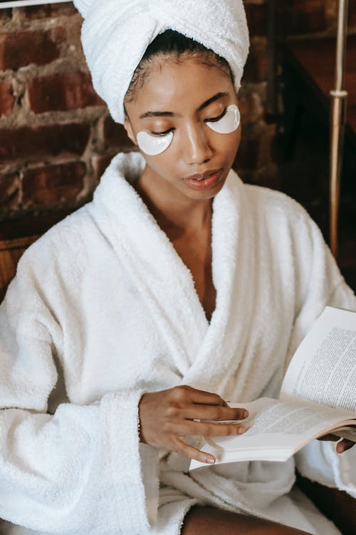 Young focused ethnic female in bathrobe and terry towel with eye patches reading textbook during procedure in spa center