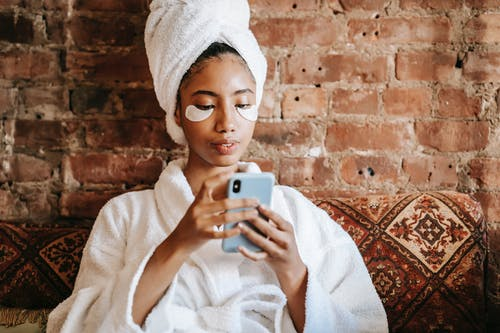 Ethnic female in robe and towel surfing internet on mobile phone during facial procedure near brick wall in house