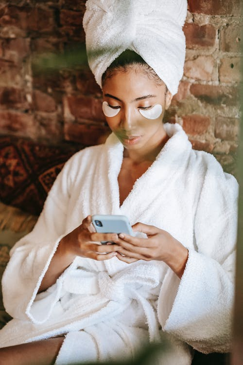Focused ethnic woman chatting on smartphone in spa center