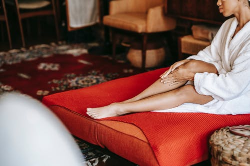 Crop anonymous barefoot ethnic female in robe applying nourishing lotion on leg while resting on red sofa in house