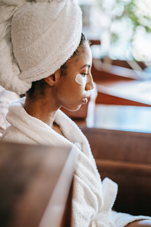 Side view of young ethnic female with terry towel on head resting in beauty salon during facial procedure