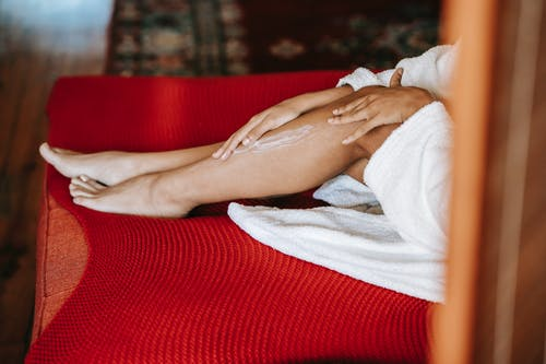 From above of crop anonymous barefoot female in robe applying moisturizing lotion on leg while sitting on red couch