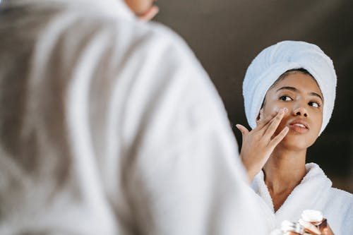 Crop ethnic woman applying cream on face against mirror