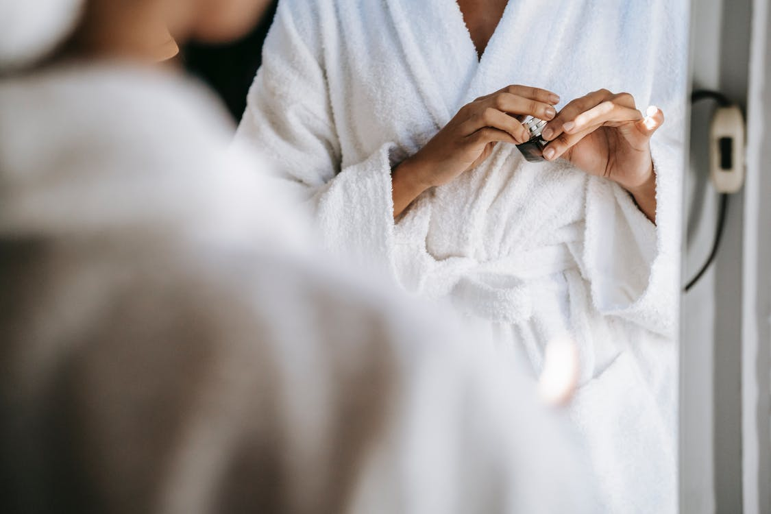 Crop unrecognizable young lady in white bathrobe opening face cream while standing in front of mirror after taking shower in morning