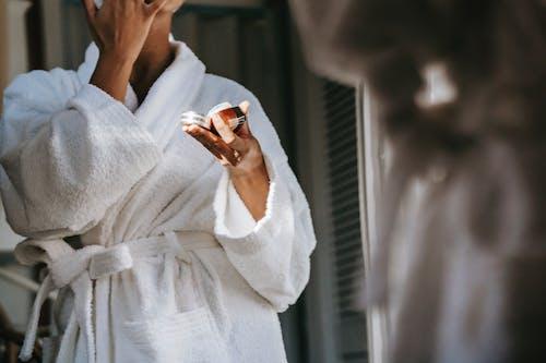 Unrecognizable ethnic woman in robe applying cream against mirror