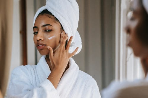 Crop attentive ethnic female in soft robe applying smear of moisturizing cream on cheek against mirror at home