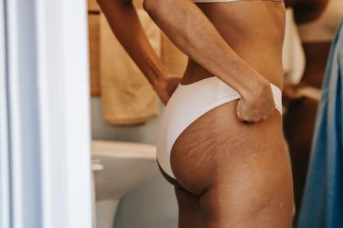 Crop slender ethnic woman in panties in bathroom