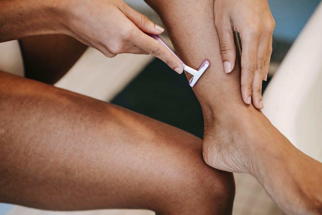 Faceless ethnic woman depilating leg with razor in bathroom