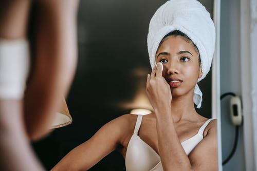 Crop young ethnic female in terry towel and brassiere cleaning face with cotton sponge while looking in mirror at home