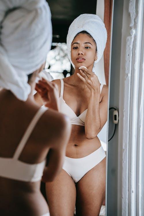 Mujer étnica En Lencería Limpiando La Cara Contra El Espejo En Casa