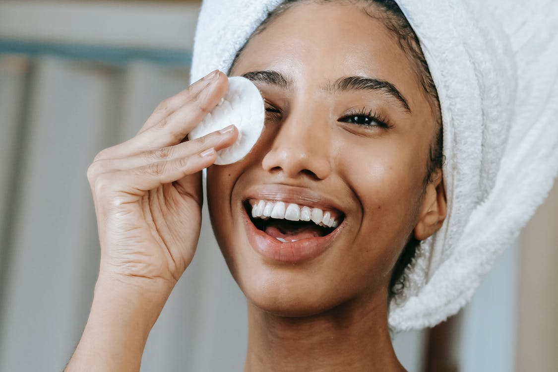 Cheerful ethnic female wrapped in towel turban moisturizing face with lotion while smiling happily