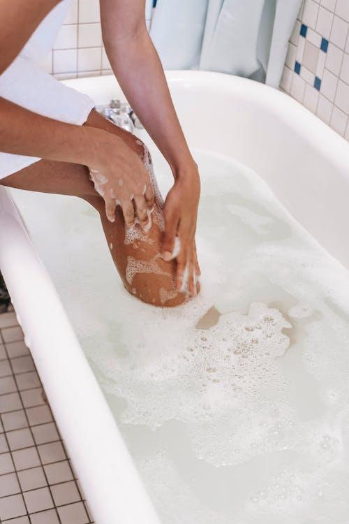 Ethnic woman washing legs in bathtub with foamy water