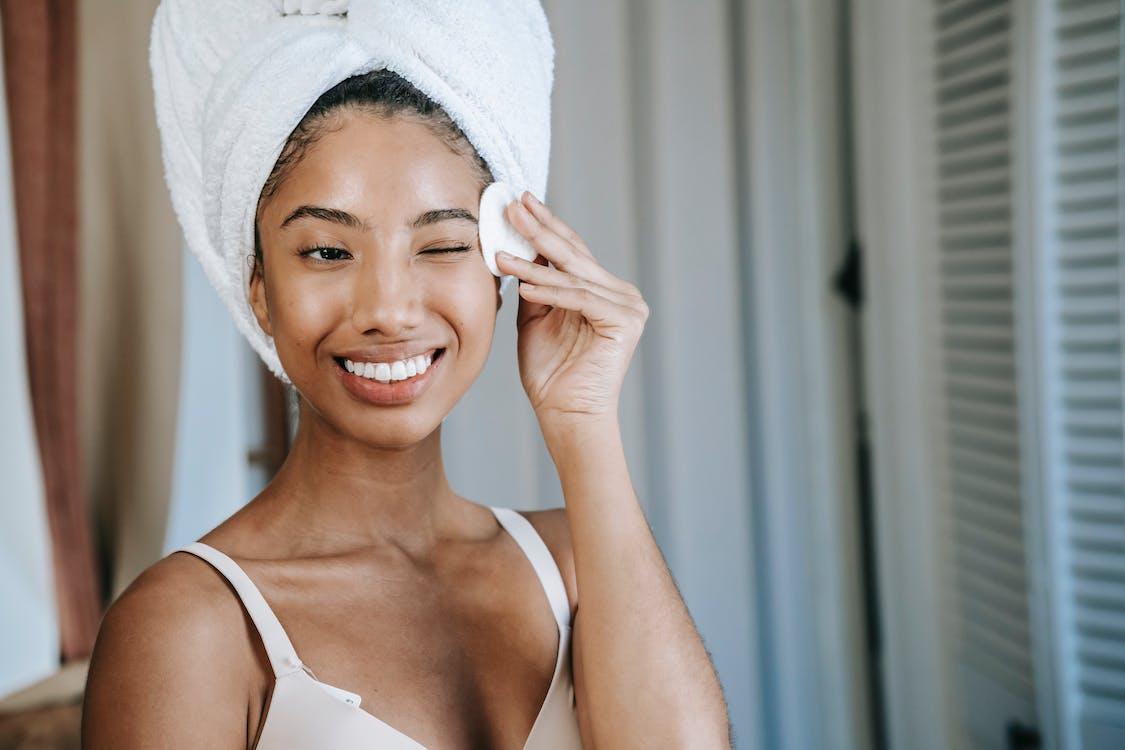 Mulher Sorridente E étnica Limpando A Pele Do Rosto Pela Manhã