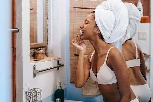 Ethnic woman cleaning teeth in bathroom