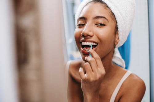 Smiling African American female with white towel on head cleaning teeth with dental flosser in bathroom