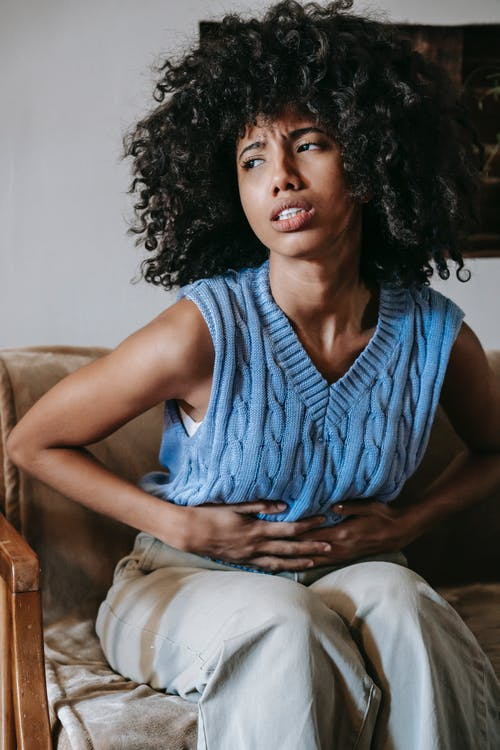 Young African American female sitting on couch at home while having acute pain in stomach