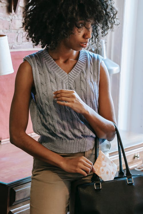 Young African American female in casual outfit putting sanitary pad in black leather handbag