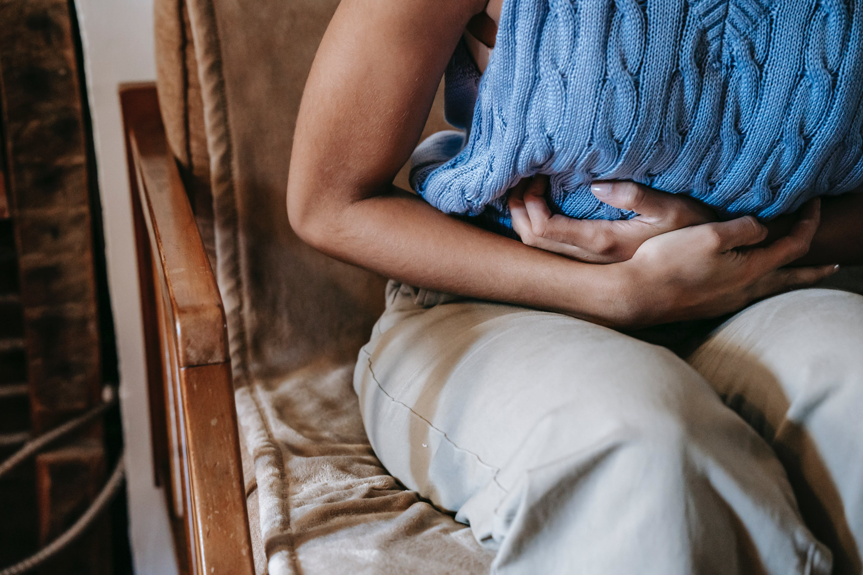 Crop unrecognizable female touching belly while having acute pain in stomach sitting on couch