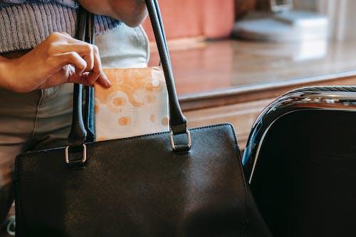 Crop woman putting panty liner in bag