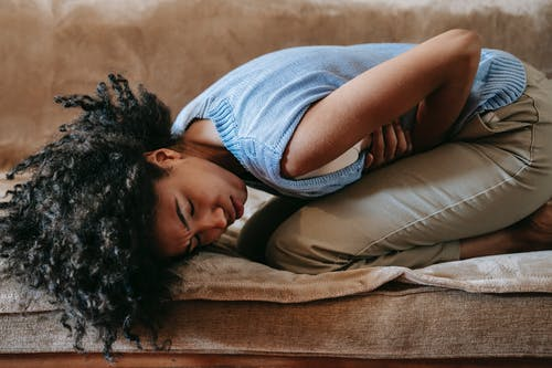 Side view of young African American female in agony on couch while having pain in stomach