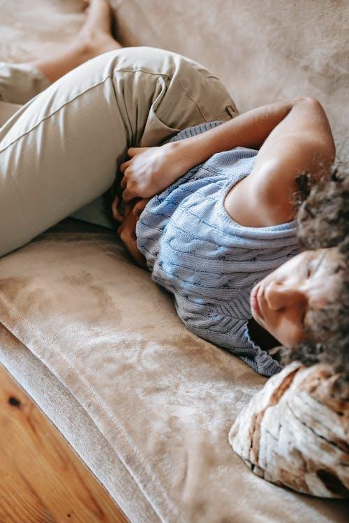 Ethnic woman feeling pain lying on sofa
