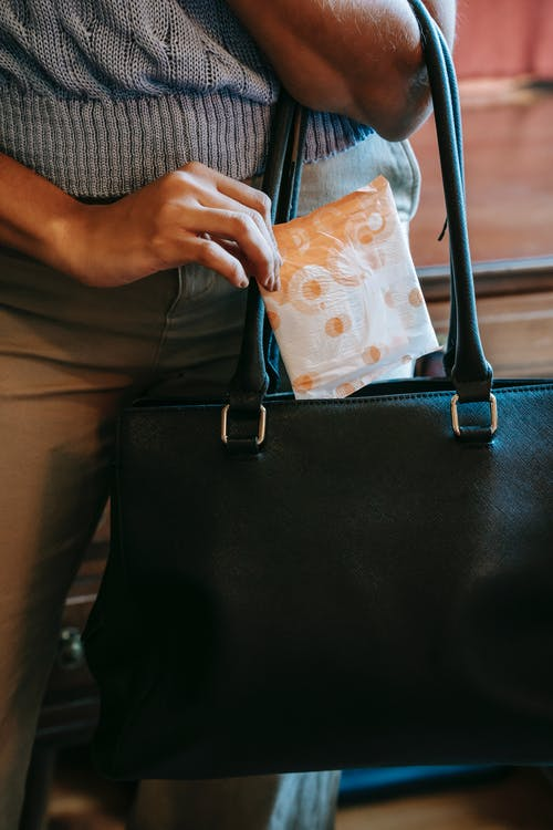 Crop faceless female in casual clothes putting panty liner in package in black leather handbag