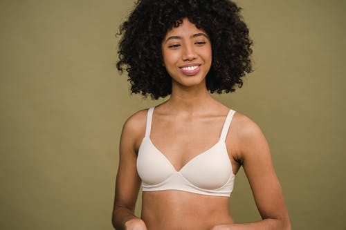 Smiling young African American female in white bra standing against olive background and looking away