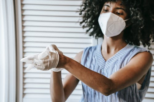Young African American female in white protective face mask putting of medical latex gloves