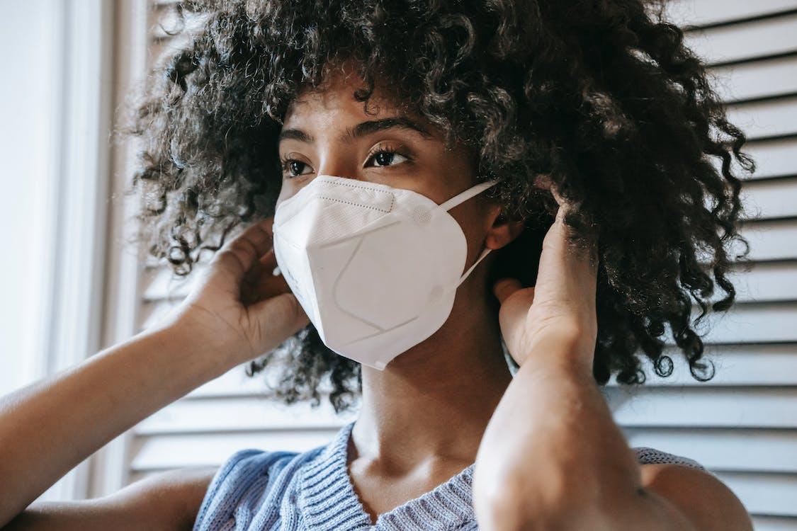 Black woman putting on respirator