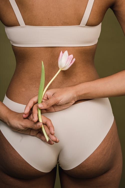 Faceless woman in lingerie holding flower behind back