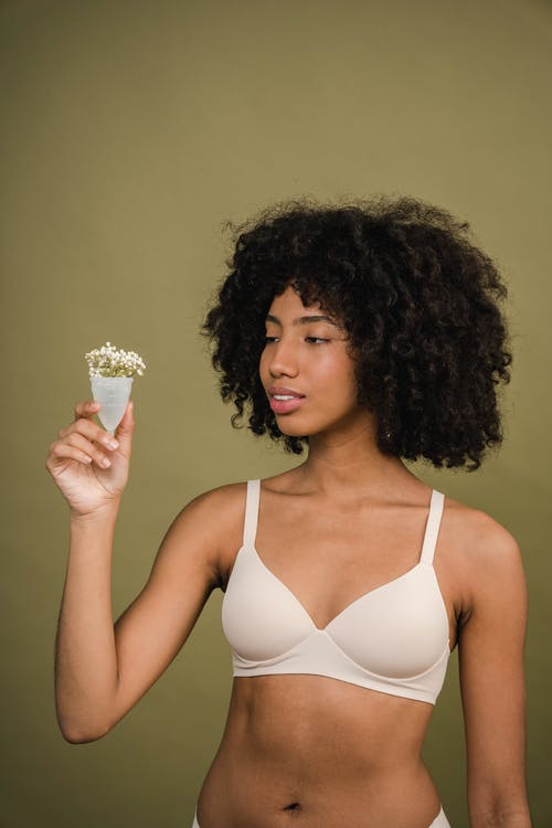 Confident young black woman with menstrual cup in hand in beige studio