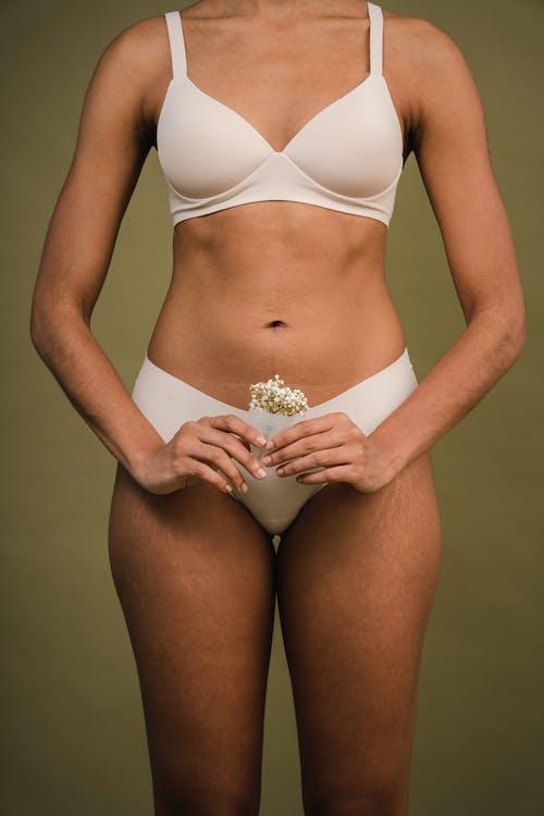 Crop female in underwear holding menstrual cup in beige studio