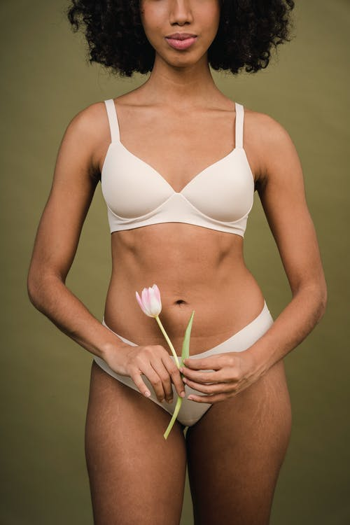 Gorgeous young African American woman in lingerie with tulip in hand in studio