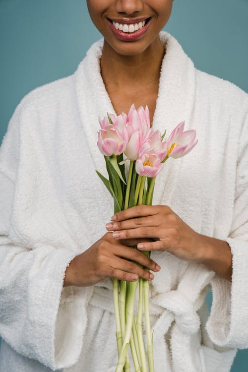 Crop anonymous cheerful African American female in bathrobe smiling and demonstrating bouquet of fresh delicate pink tulips