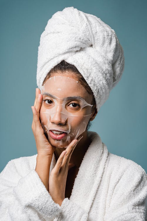 Ethnic female in towel on head applying face mask