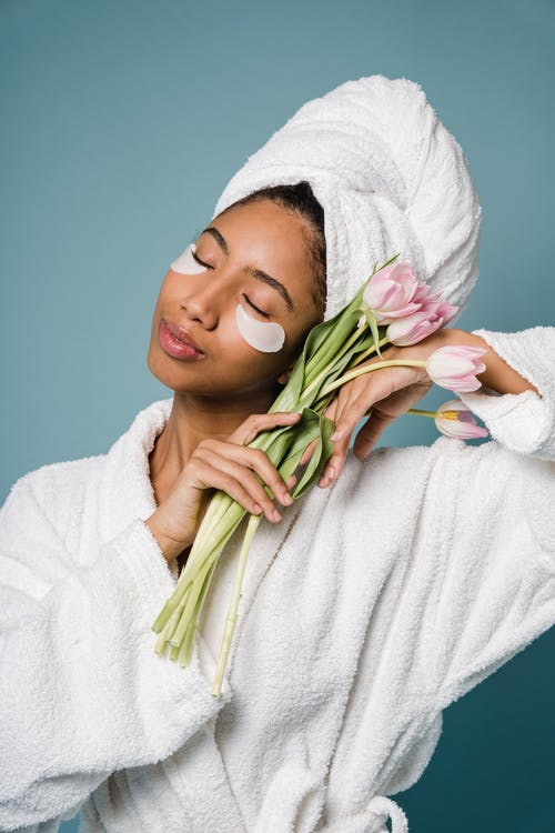 Tranquil African American female with eye patches in white bathrobe and towel on head standing with closed eyes and bouquet of tulips against blue background