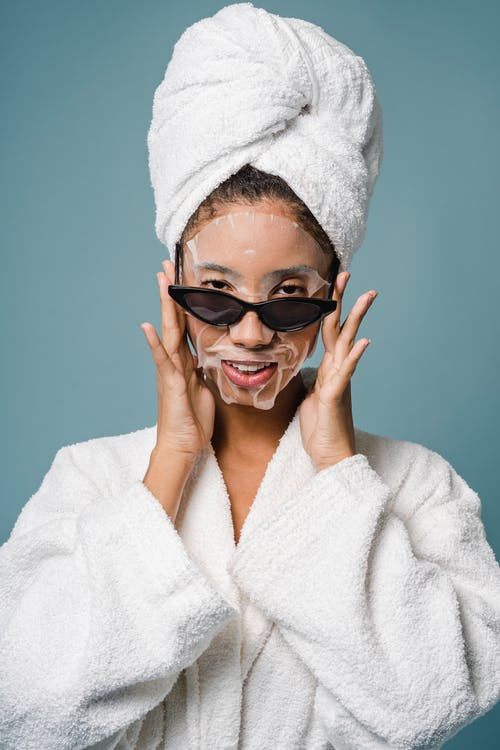 Positive African American female with sheet mask in sunglasses and bathrobe