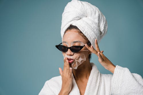 Calm African American woman with moisturizing sheet mask in sunglasses and white towel turban on head touching dace against blue background in studio