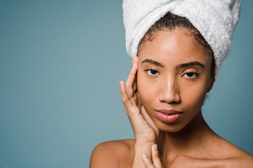 Black woman in white towel turban touching face and looking at camera