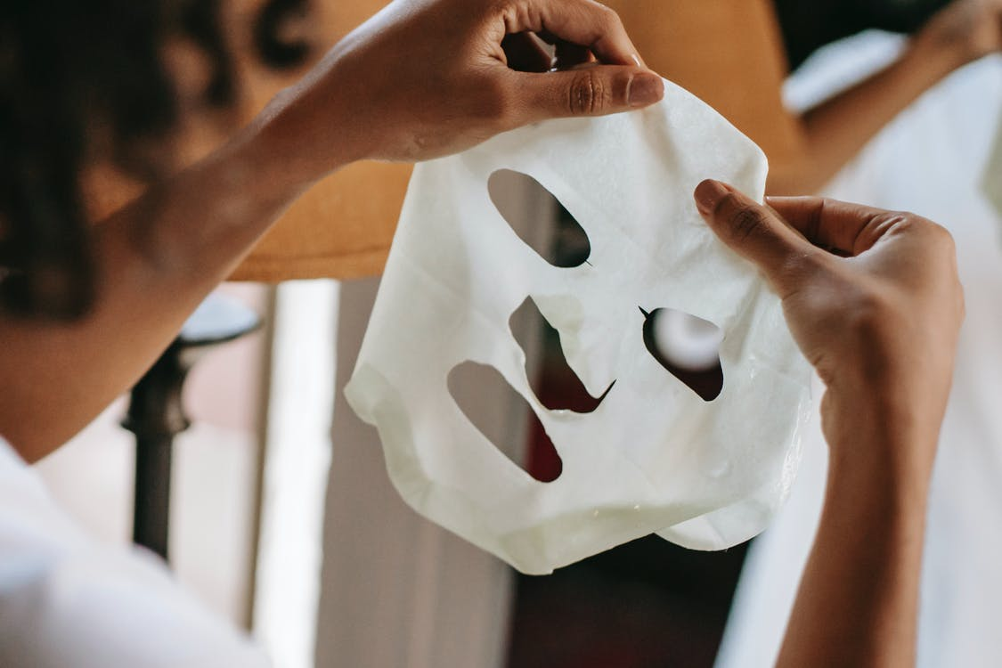 Ethnic female holding sheet mask at home