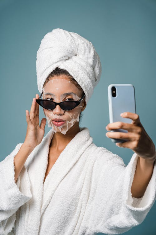 Confident black female with sheet mask taking selfie on smartphone