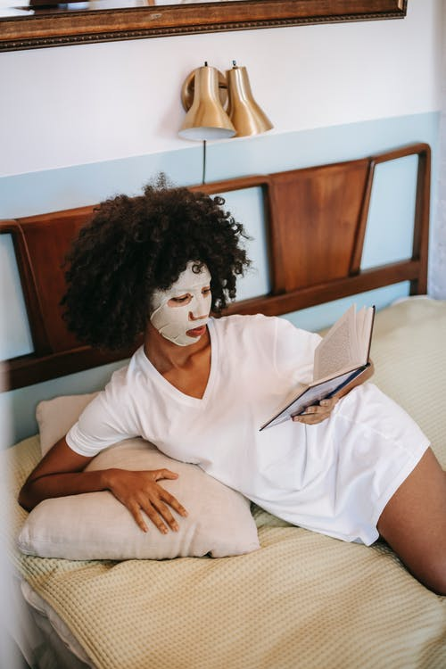 African American female in sheet mask reading book in bedroom